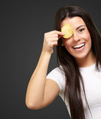 Portrait of young woman holding a potato chip in front of her ey — ストック写真