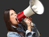 Portrait of young woman screaming with megaphone against a black — Stock Photo
