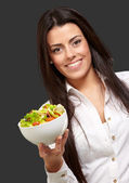 Portrait of young woman holding salad over black — Stock Photo