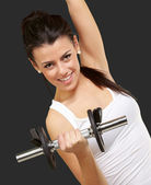 Portrait of young woman doing fitness with weights over black ba — Stock Photo