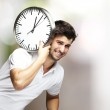 Portrait of a handsome young man carrying a clock against a blurry background — Stock Photo