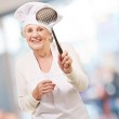 Portrait of sweet senior cook woman holding a metal spoon indoor — Stock Photo