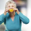 Portrait of senior woman holding a orange slice in front of her — Stock Photo #11367748