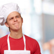Young cook man having a idea against a abstract background — Stock Photo