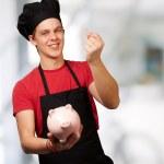 Ritratto di uomo giovane cuoco tenendo moneta euro e salvadanaio indo — Foto Stock #11367900