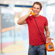 Portrait of young man talking with vintage telephone indoor — Stock Photo