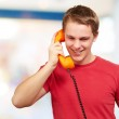 Portrait of young man talking on vintage telephone indoor — Stock Photo