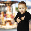 Portrait of adorable kid touching his stomach against a carousel - Stockfoto
