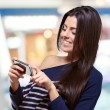 Portrait of young woman touching a modern mobile indoor - Stock Photo
