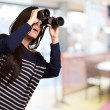 Portrait of young girl looking through a binoculars indoor — Stock Photo #11368235