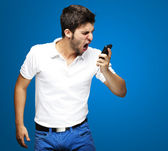 Portrait of angry young man shouting using mobile over blue background — Stock Photo