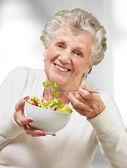 Retrato de mujer senior comiendo una ensalada fresca interior — Foto de Stock
