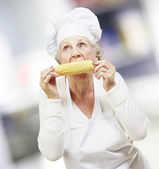 Senior woman cook eating a corncob, indoor — Stock Photo