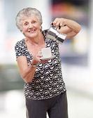 Portrait of a vitality senior woman serving a tea cup indoor — Stock Photo