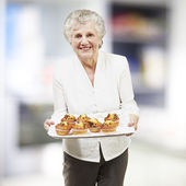 Senior woman smiling and holding a tray with muffins, indoor — Foto de Stock