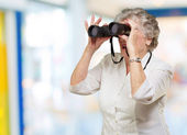Portrait de femme senior regardant dans un intérieur de jumelles — Photo