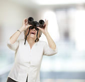 Portrait of senior woman looking through a binoculars, indoor — Stock Photo