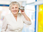 Portrait of senior woman hearing with metal tin can indoor — Stock Photo