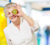Portrait of senior woman holding kiwi in front of her eye indoor — Stock Photo