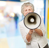 Portrait of senior woman screaming with megaphone at crowded pla — Stock Photo