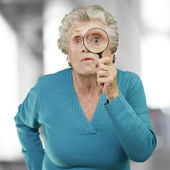 Portrait of senior woman looking through a magnifying glass, ind — Stock Photo
