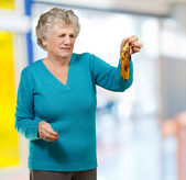 Senior woman holding a rotten banana indoor — Stock Photo