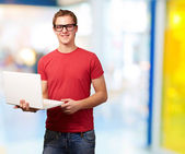 Portrait of young student man holding laptop in classroom — Foto de Stock