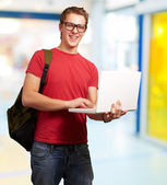 Portrait of young man holding laptop and wearing backpack indoor — Stok fotoğraf