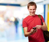 触摸手机屏幕室内的年轻男子的画像 — 图库照片