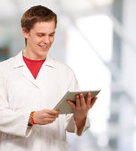 Portrait of young academic holding a digital tablet at entrance — Stockfoto