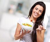 Portrait of healthy woman eating salad indoor — Stock Photo