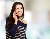 Young girl talking on mobile indoor — Stock Photo