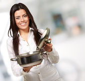 Portrait of young girl opening sauce pan indoor — Stock Photo