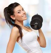 Retrato de una mujer bastante joven sosteniendo pesas y haciendo condic — Foto de Stock