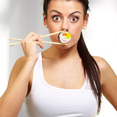 Young woman covering her mouth with a sushi piece, indoor — Stock Photo