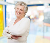 Portrait of senior woman smiling at a modern building — Stock Photo