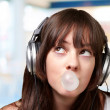 Portrait of young woman listening to music with bubble gum over — Stock Photo