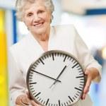 Portrait of a happy senior woman holding clock indoor — Stock Photo