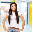 Portrait of young woman holding green apple on her head indoor — Stock Photo