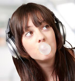 Portrait of young woman listening to music with bubble gum indoo — Stock Photo