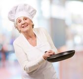 Portrait of a friendly cook senior woman holding pan indoor — Stock Photo