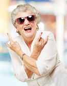 Portrait of senior woman smiling and wearing sunglasses against — Stock Photo