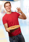 Portrait of young man holding pizza and doing good gesture indoo — Stock Photo
