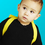 Portrait of adorable kid carrying yellow backpack over blue back — Stock Photo