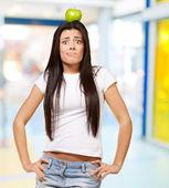 持有在她头上的青苹果室内的年轻女人肖像 — 图库照片