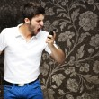 Royalty-Free Stock Photo: Portrait of angry young man shouting using mobile against a vint