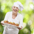 Senior woman cook holding a tray with muffins against a nature b — Stock Photo #11580740