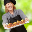 Portrait of cook woman showing a homemade muffins tray against a — Stock Photo #11580837
