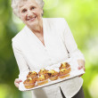 Senior woman smiling and holding a tray with muffins against a n — Stock Photo #11580898