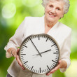 Portrait of a happy senior woman holding clock against a nature - 图库照片